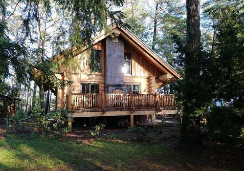 """Naturstammhaus """"Tucker"""" - Blick auf Giebel mit Terrasse und Schornstein"""